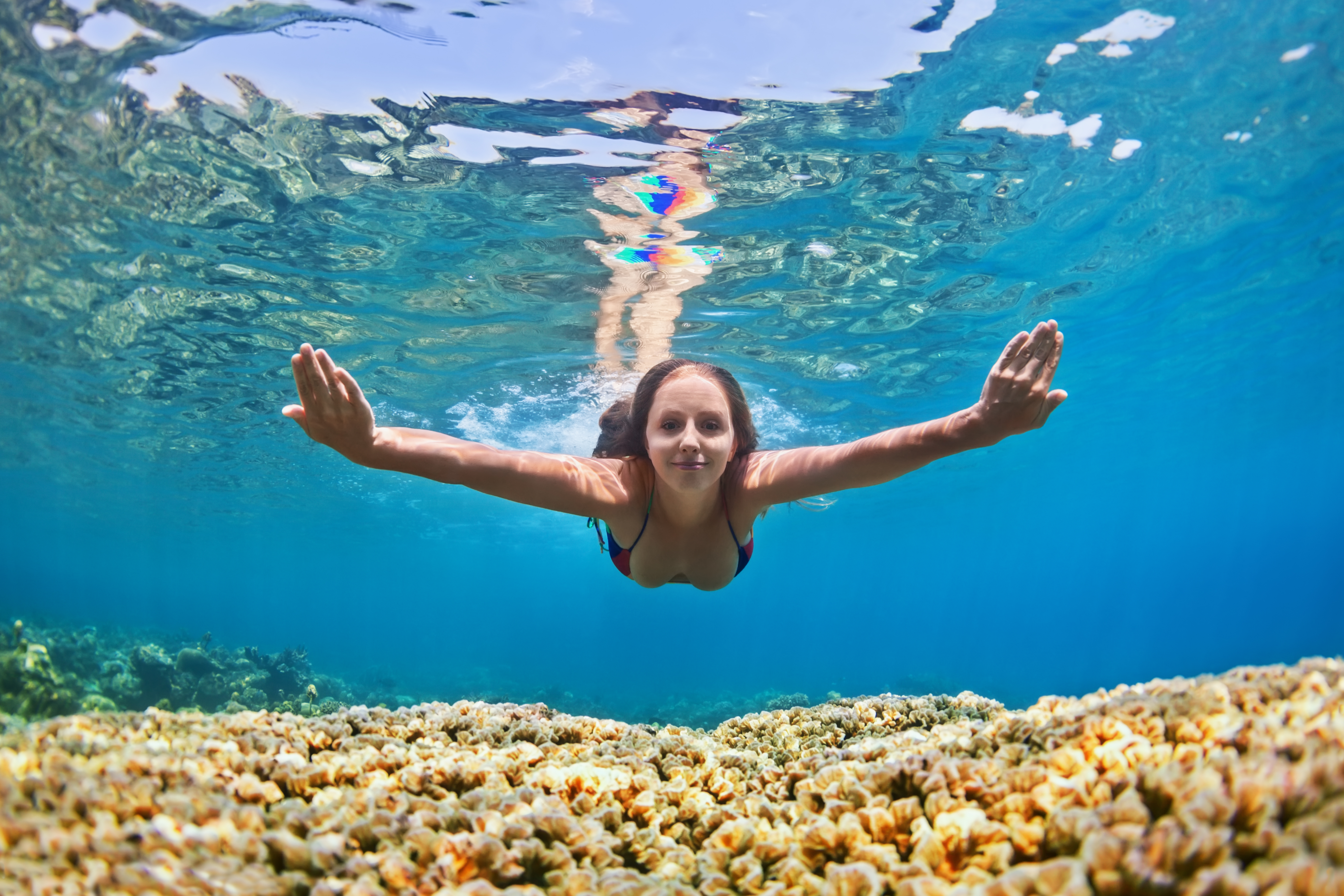 Happy beautiful girl - young woman dive underwater with fun over coral reef in sea pool. Healthy active lifestyle people water sport outdoor activity and swimming lessons on beach summer holidays.